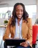 Zekere vrouwelijke ontwerper die aan een digitale tablet in rode creatieve bureauruimte werken Stock Fotografie