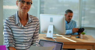 Zekere vrouwelijke uitvoerende zitting bij haar bureau stock video