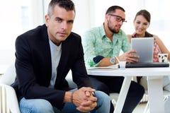 Zekere zakenman in bureau met zijn team Stock Foto