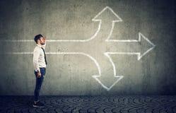 Zekere zakenman die de toekomst onderzoeken bij kruispunt stock afbeelding