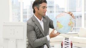 Zekere zakenman die een aardse bol bekijken stock videobeelden