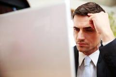 Zekere zakenman die laptop met behulp van Stock Foto