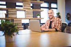 Zekere zakenman die laptop met behulp van bij bureau Royalty-vrije Stock Afbeeldingen