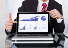Zekere zakenman die laptop tonen bij bureau Stock Foto