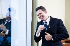 Zekere zakenman die zich in bureau door venster bevindt Royalty-vrije Stock Afbeelding