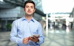 Zekere zakenman die zijn tablet gebruiken Stock Foto's