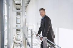 Zekere Zakenman Standing By Railing Stock Foto's