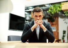 Zekere zakenmanzitting bij de lijst stock afbeelding