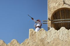 young man holding his rifle while standing on high Wall stock photo
