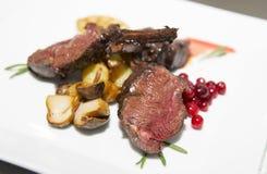 Zeldzaam gekookt lapje vlees met gebraden paddestoelen stock afbeelding