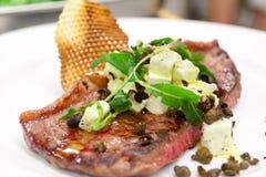 Zeldzaam gekookt lapje vlees met kappertjes en kaasbovenste laagje stock foto's