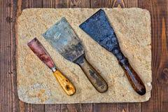 Zeldzame de messen macromening van de stopverfspatel de bouw van decorateurhulpmiddelen op steenplaat en houten lijstachtergrond Stock Afbeeldingen
