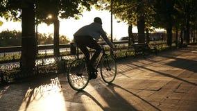 Zeldzame menings jonge mens die een fiets in het ochtendpark of boulevard cirkelen door bedekte weg Langzame motie van jong perso stock video
