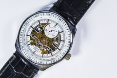 Zelenodolsk, Ukraine, on January 5, 2019. The men`s watch with a leather black thong and gold gears and the white dial lies. stock photography