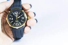 Zelenodolsk, Ukraine, on January 5, 2019. The men`s wrist black watch with a rubber thong and the gold dial. stock image