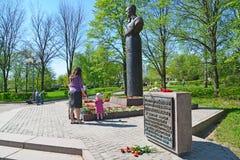 Zelenograd, Rusia - 9 de mayo 2016 Mamá e hija que ponen las flores en el monumento para formar a Rokossovsky en Victory Park Fotos de archivo libres de regalías