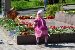 Zelenograd, Rusia - 9 de mayo 2016 Niña que pone las flores en el monumento para formar a Rokossovsky en Victory Park Foto de archivo libre de regalías