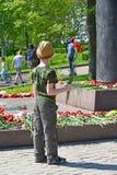 Zelenograd, Rusia - 9 de mayo 2016 Niño pequeño que pone las flores en el monumento para formar a Rokossovsky en Victory Park Fotografía de archivo