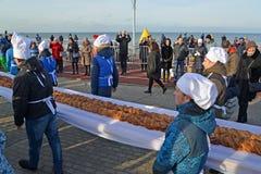 Zelenogradsk,俄罗斯 男性面包师在堤防负担长甜的饼18米 Krantsevsky饼节日  图库摄影