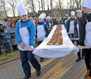 Zelenogradsk,俄罗斯 男性面包师负担长甜的饼18米 Krantsevsky饼节日  免版税库存照片