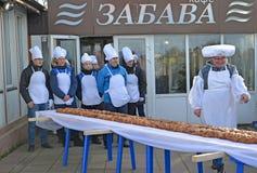 Zelenogradsk,俄罗斯 面包师在长甜的饼附近站立18米 Krantsevsky饼节日  免版税图库摄影