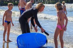 ZELENOGRADSK, KALININGRAD REGION, RUSSIA - JULY 29, 2017: Unknown young girl is standing next to a surf instructor. Unknown young girl is standing next to a Royalty Free Stock Photography