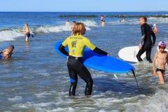ZELENOGRADSK, KALININGRAD-REGION, RUSSLAND - 29. JULI 2017: Unbekannte Surfer mit dem Surfbrett, das nahe unbekannten Kindern ste Stockbild