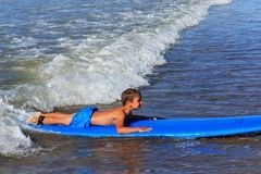ZELENOGRADSK, KALININGRAD-REGION, RUSSLAND - 29. JULI 2017: Unbekannter Junge auf dem Surfbrett, das vom Surfen stillsteht und le Stockbild