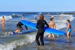 ZELENOGRADSK, KALININGRAD-REGION, RUSSLAND - 29. JULI 2017: Unbekannter Surfer mit dem Surfbrett, das nahe unbekannten Kindern st Lizenzfreies Stockbild