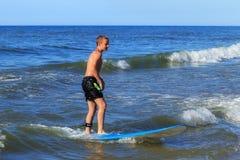 ZELENOGRADSK KALININGRAD REGION, RYSSLAND - JULI 29, 2017: Okänd pojke på surfingbrädan som vilar och lär av att surfa Arkivbild