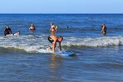 ZELENOGRADSK KALININGRAD REGION, RYSSLAND - JULI 29, 2017: Okänd pojke på surfingbrädan som vilar och lär av att surfa Royaltyfri Foto