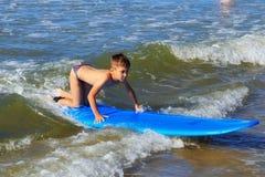 ZELENOGRADSK KALININGRAD REGION, RYSSLAND - JULI 29, 2017: Okänd pojke på surfingbrädan som vilar och lär av att surfa Arkivfoto