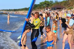 ZELENOGRADSK KALININGRAD REGION, RYSSLAND - JULI 29, 2017: Okänd surfare med surfingbrädaanseende på en sandig strand Arkivbild