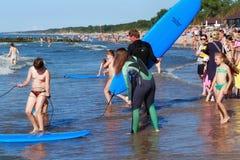 ZELENOGRADSK KALININGRAD REGION, RYSSLAND - JULI 29, 2017: Okända surfare med surfingbrädaanseende på en sandig strand Arkivfoton