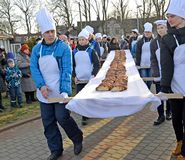ZELENOGRADSK, RUSSIA. Male bakers bear sweet pie 18 meters long. Festival of Krantsevsky pie royalty free stock photo
