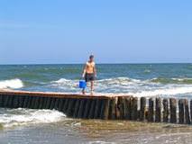 Zelenogradsk, Russland Der junge Mann geht auf einen alten Wellenbrecher mit einem Wassereimer Lizenzfreie Stockbilder