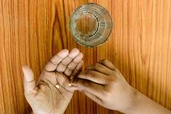 Zelf-behandeling thuis vanaf voorgeschreven door arts Een gietende geneeskunde van de tienerjongen in haar hand Medisch, gezondhe stock foto