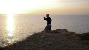 Zelf-defensie opleiding, bokser mannelijke het praktizeren vuiststrijd vóór de concurrentie op heuvel dichtbij overzees stock videobeelden