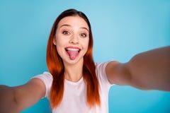 Zelf-portret van haar zij aardig aantrekkelijk mooi aantrekkelijk vrolijk vrolijk gek meisje die witte t-shirt dragen die tong to stock afbeelding