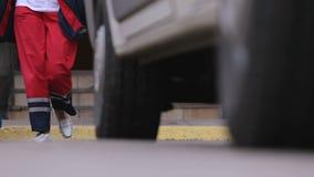 Zelf-verzekerde ziekenwagen artsen die ziekenhuis verlaten, die voor noodoproep, hulp het gaan stock video