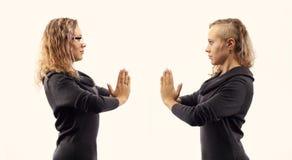Zelfbesprekingsconcept Jonge vrouw die aan zich spreken, tonend gebaren Dubbel portret van twee verschillende zijaanzichten Royalty-vrije Stock Foto's