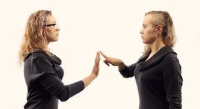 Zelfbesprekingsconcept Jonge vrouw die aan zich spreken, tonend gebaren Dubbel portret van twee verschillende zijaanzichten Stock Fotografie