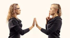 Zelfbesprekingsconcept Jonge vrouw die aan zich spreken, tonend gebaren Dubbel portret van twee verschillende zijaanzichten Royalty-vrije Stock Foto
