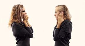 Zelfbesprekingsconcept Jonge vrouw die aan zich spreken, tonend gebaren Dubbel portret van twee verschillende zijaanzichten stock afbeelding