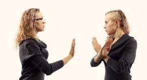 Zelfbesprekingsconcept Jonge vrouw die aan zich spreken, tonend gebaren Dubbel portret van twee verschillende zijaanzichten Stock Afbeeldingen
