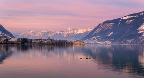 Free Zell Am See In Winter Evening. View Of Lake Zell, Town, Mountains And Snow With Reflections In Water. Alpine Town At Stock Photos - 202462873