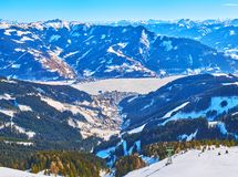 Zell am See resort and Zeller lake from Schmitten mount, Austria. Spectacular view from the peak of Schmitten mount on the snowy Alps of Kaprun and Zell am Zee royalty free stock photo