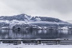 Zell am See Salzburg - Austria Cold and frozen lake with large snowy mountains on background and fog clouds above. Zell am See Salzburg - Austria Cold and Royalty Free Stock Photos
