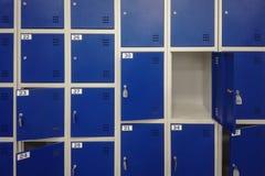 Zellen in einer blauen Farbgepäckaufbewahrung mit Schlüsseln und einem Hintergrund der offenen Tür stockbild