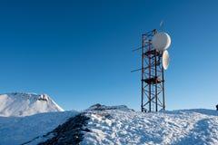 Zelluläre Kommunikationsstation in den Schnee-mit einer Kappe bedeckten Bergen Stockbild
